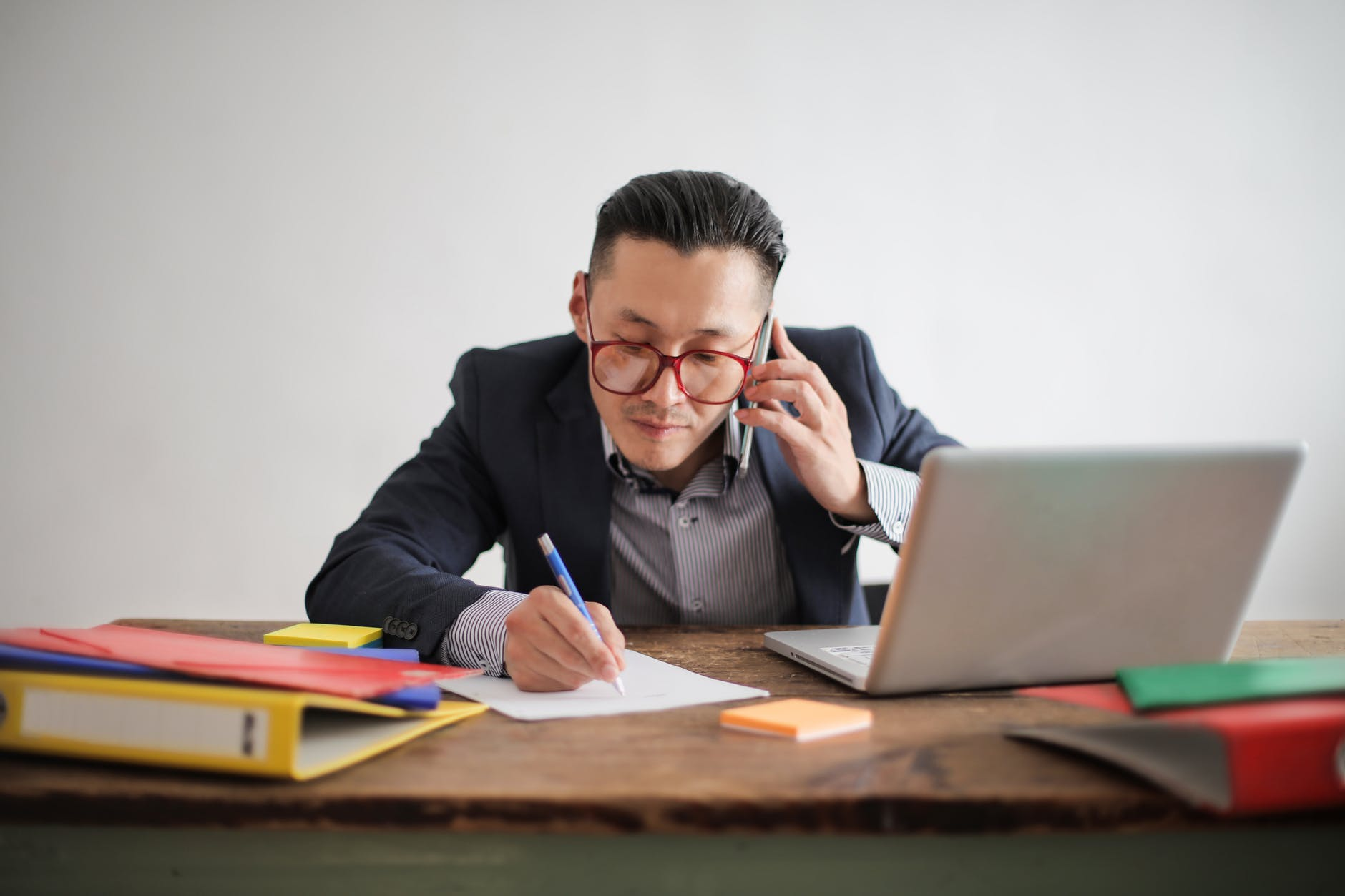 photo of man in blue suit jacket striped shirt and eyeglasses talking on the phone while sitting at a table with his laptop