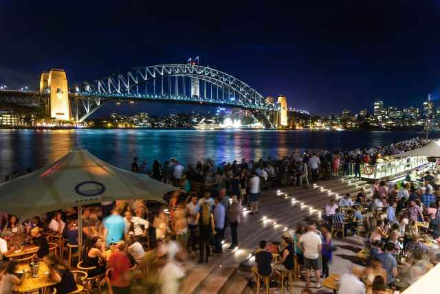 people sitting and standing near bridge during nighttime